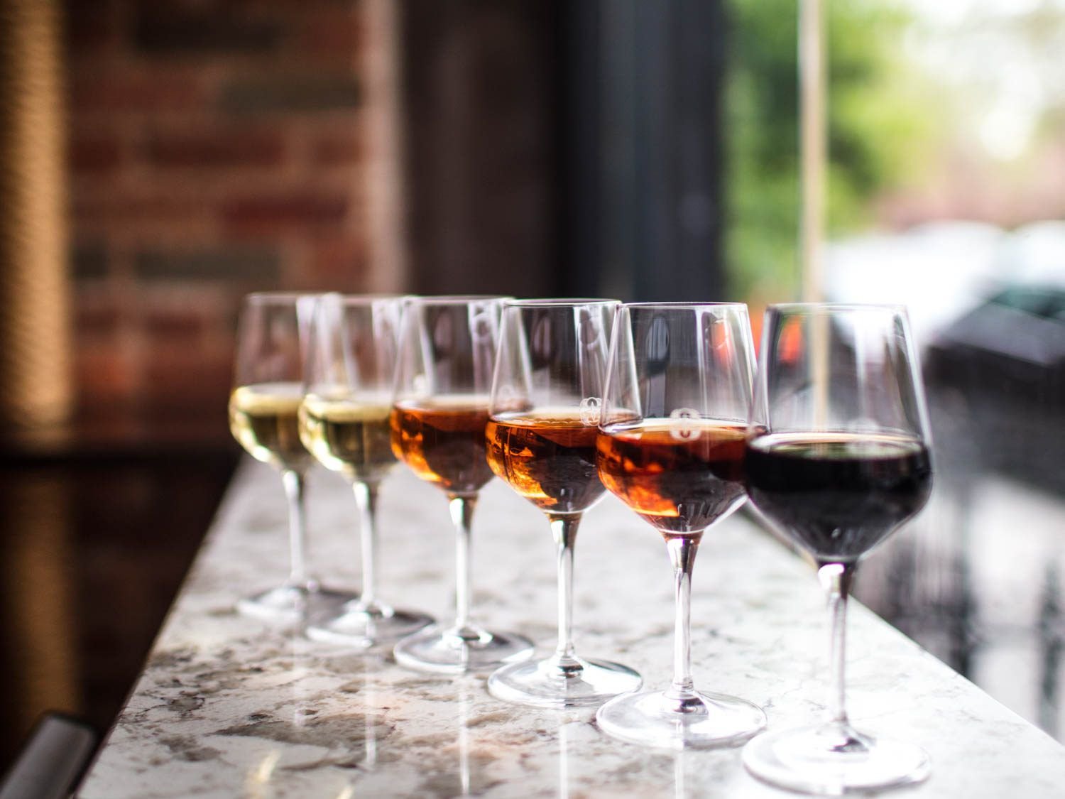 A diagonal line of wineglasses containing a range of sherries, from light to dark, on a marble countertop