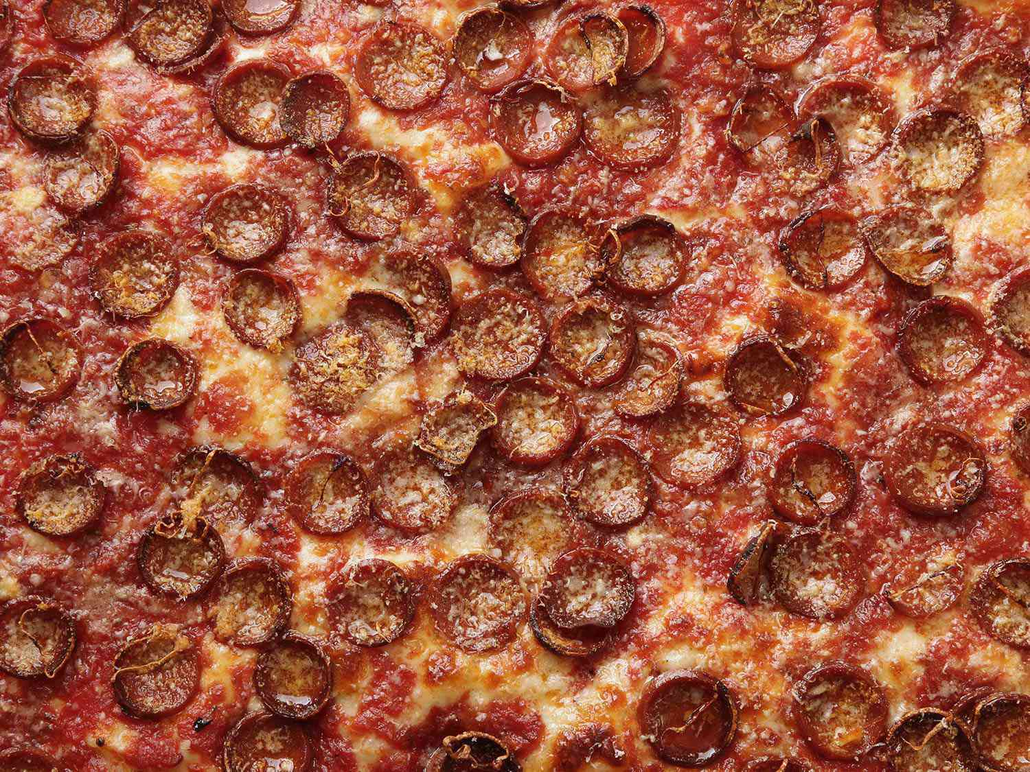 Close-up of pepperoni on top of Sicilian-style pizza