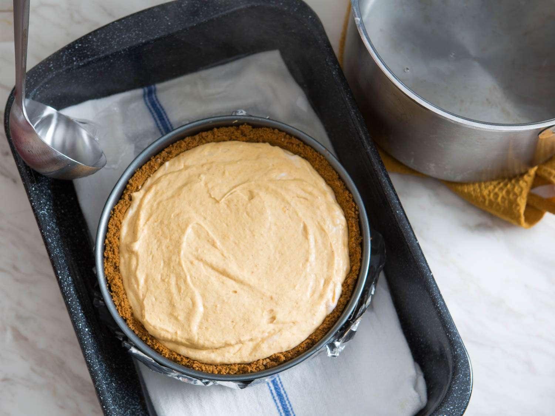 Adding boiling water to roasting pan around pumpkin cheesecake in a springform pan before baking.