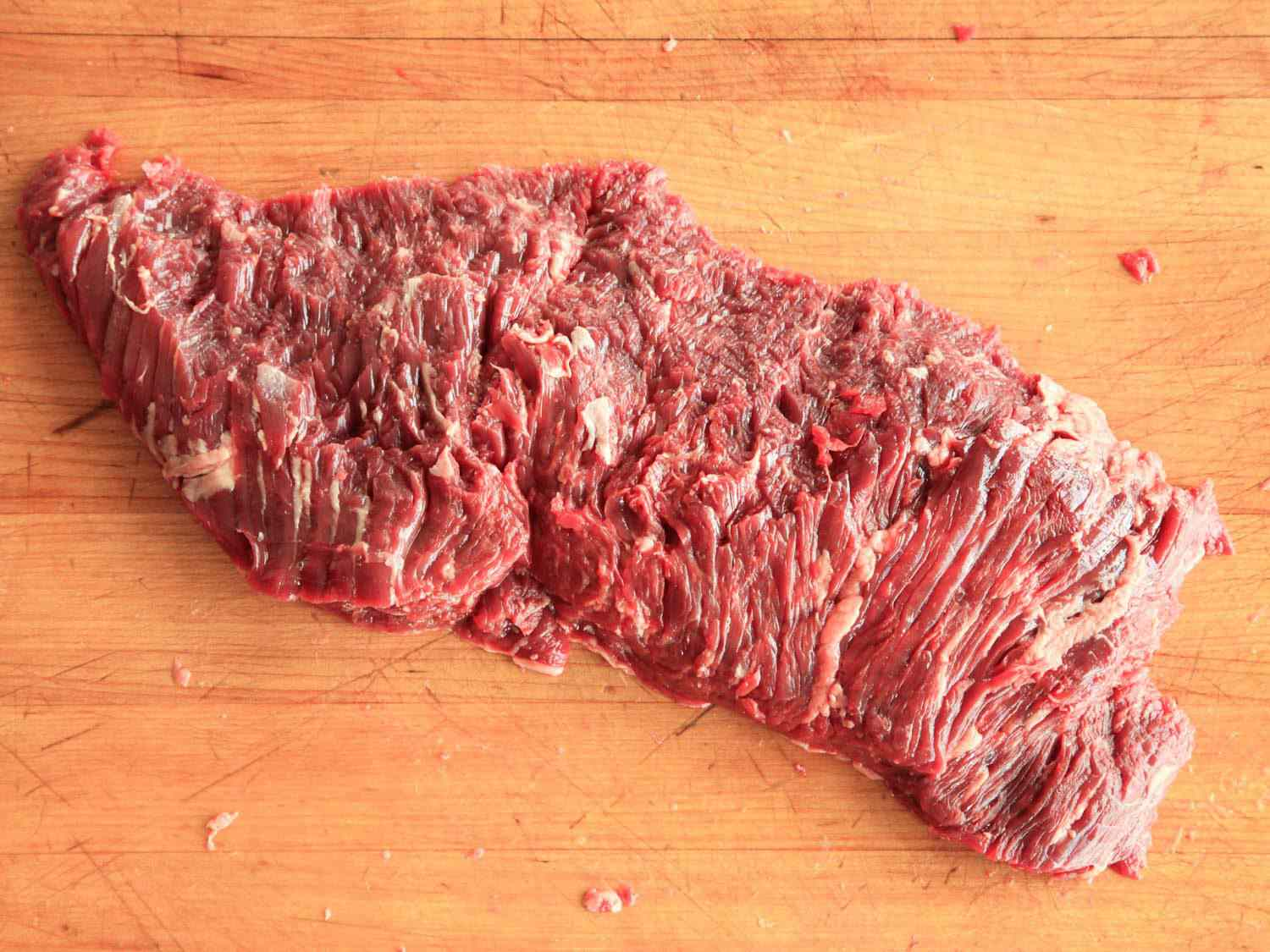 Inexpensive cut of flap steak on a wooden cutting board.