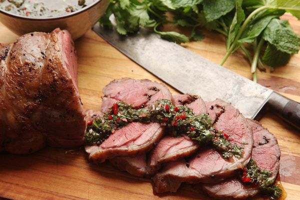 Sous vide lamb leg sliced up topped with chimichurri sauce