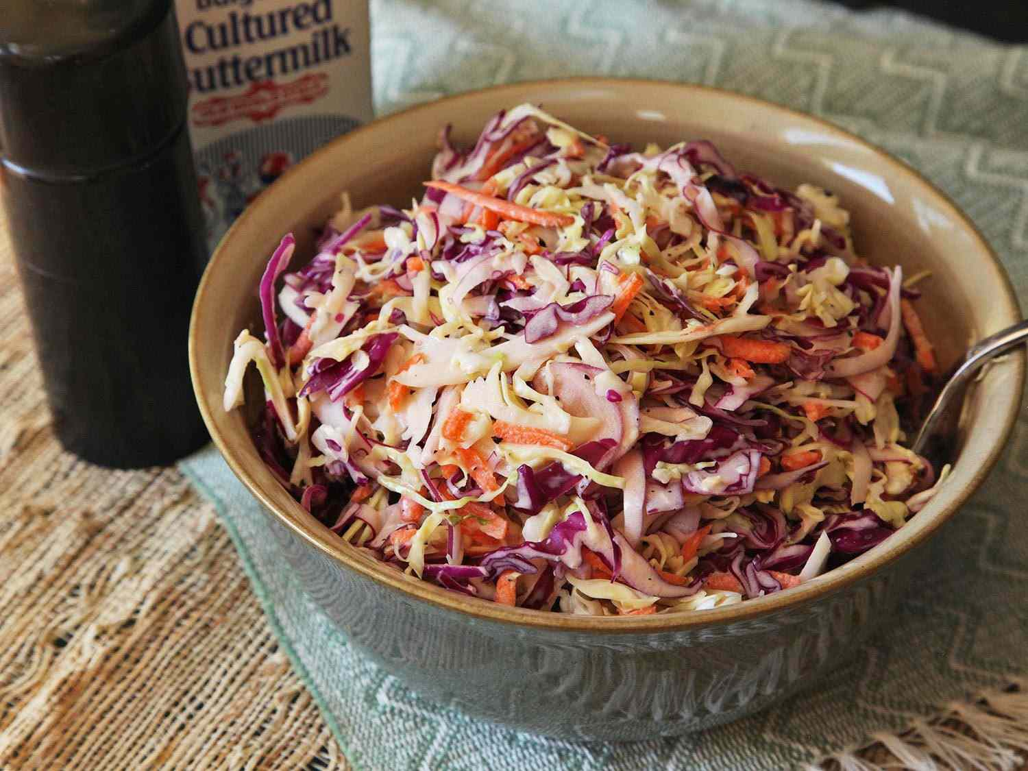 A bowl of Super-Simple Tangy Buttermilk Coleslaw, made with red and green cabbage and carrots