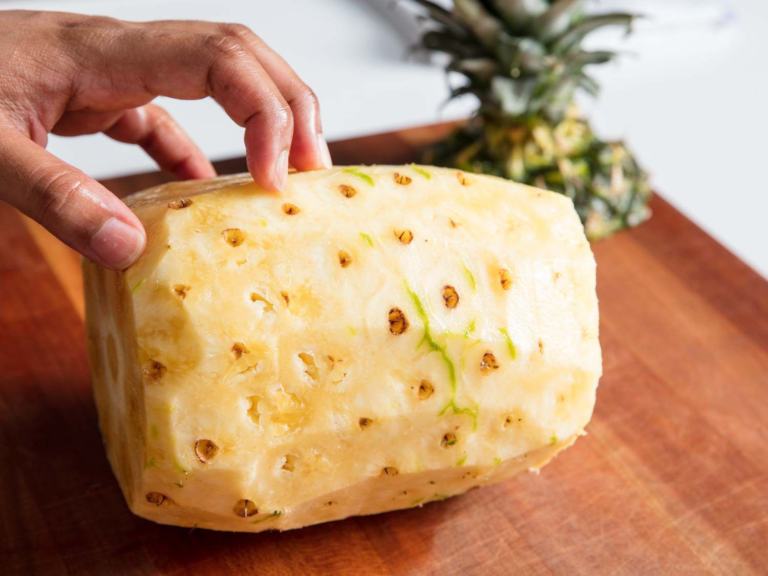 A pineapple with the sides trimmed off on a cutting board.