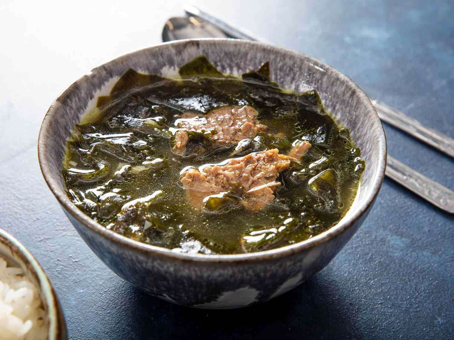 A bowl of Korean seaweed soup (miyeok guk) with pieces of brisket visible in the broth