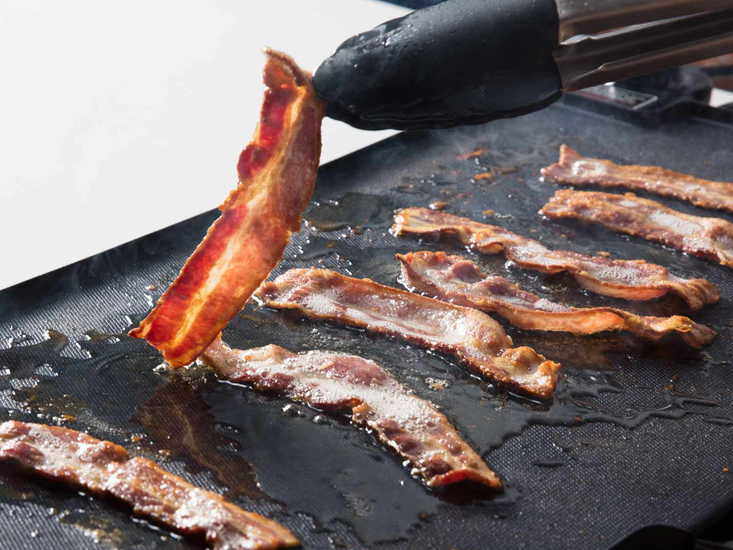 Turning bacon on an electric griddle.