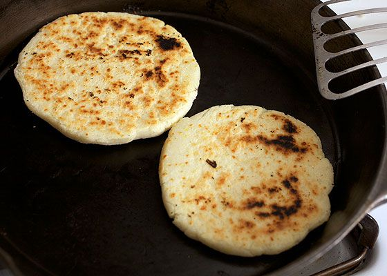 Two arepas being cooked in a cast iron skillet.