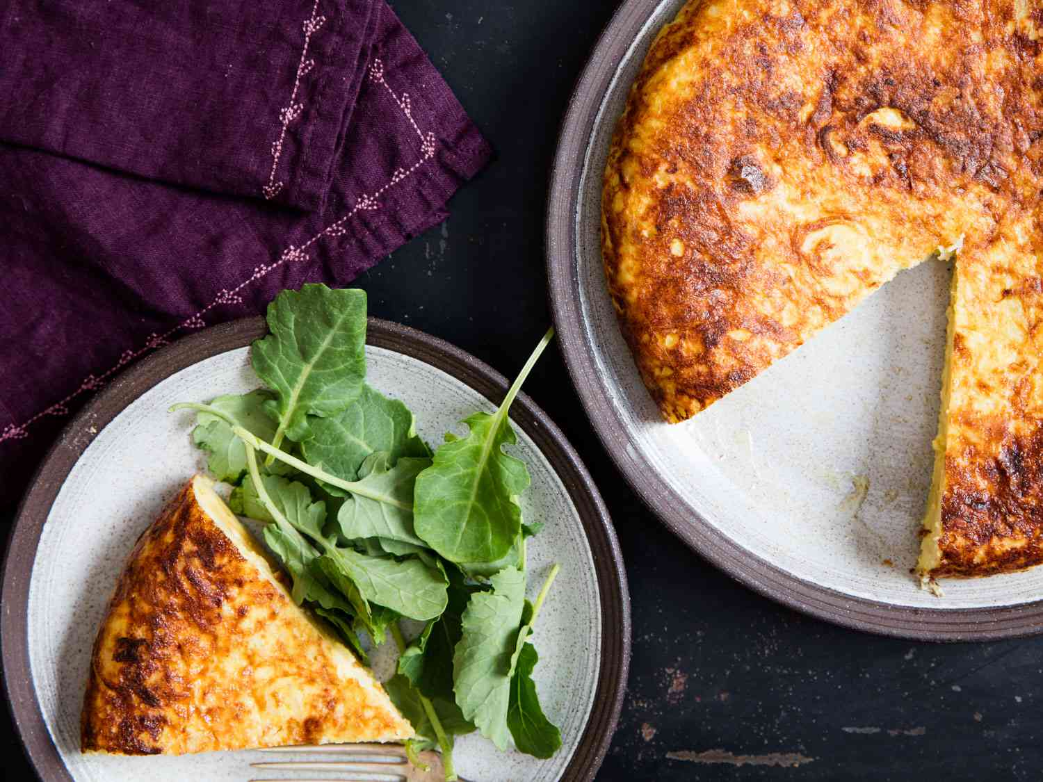 Slice of potato and onion Spanish tortilla on a plate with salad and the rest of the tortilla on the side.