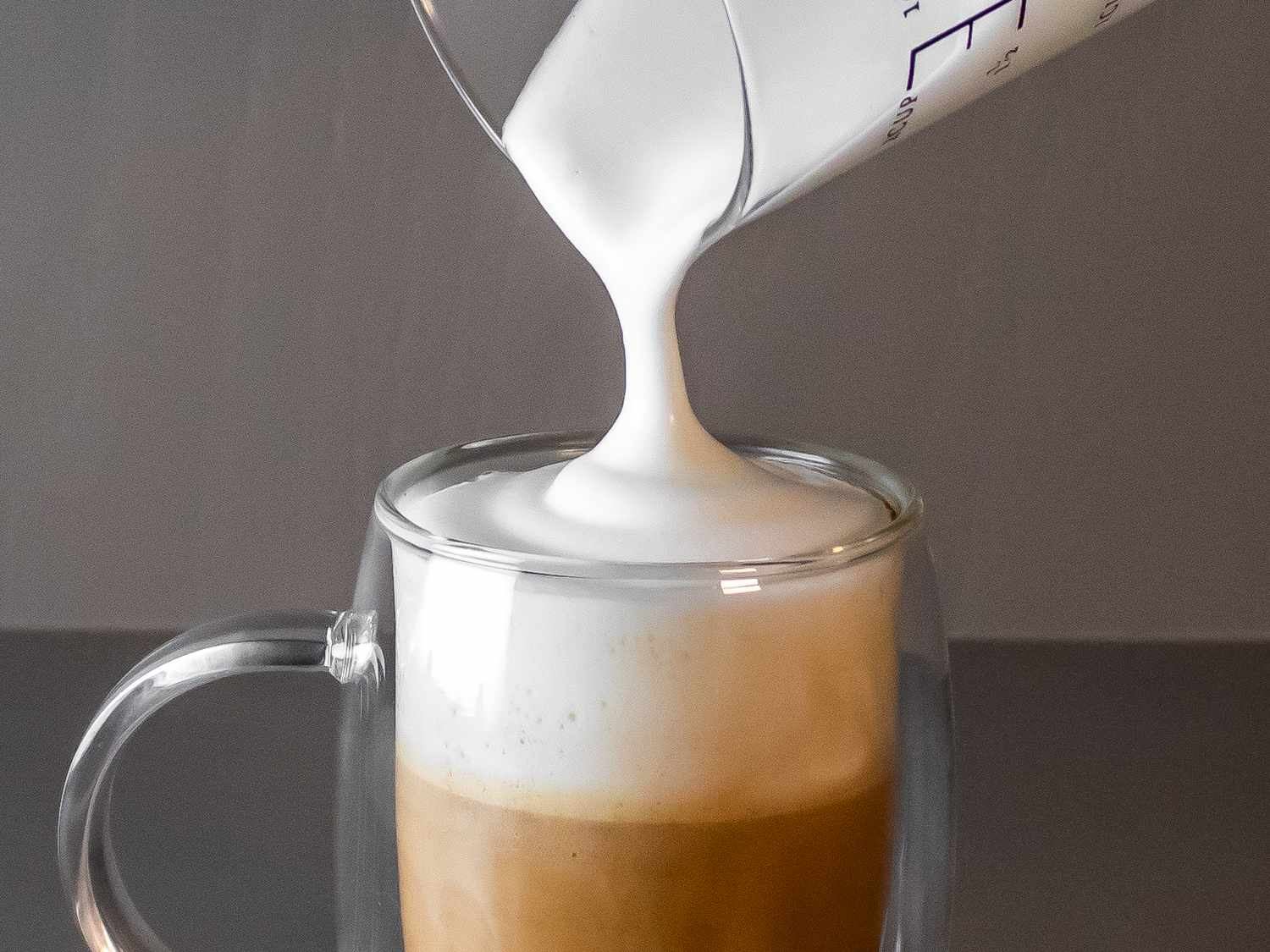 a close up of milk foam being poured into a coffee cup
