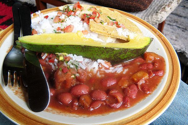 Colombian style beans and rice, bandeja paisa, with aji (Colombian style salsa) and an avocado wedge.