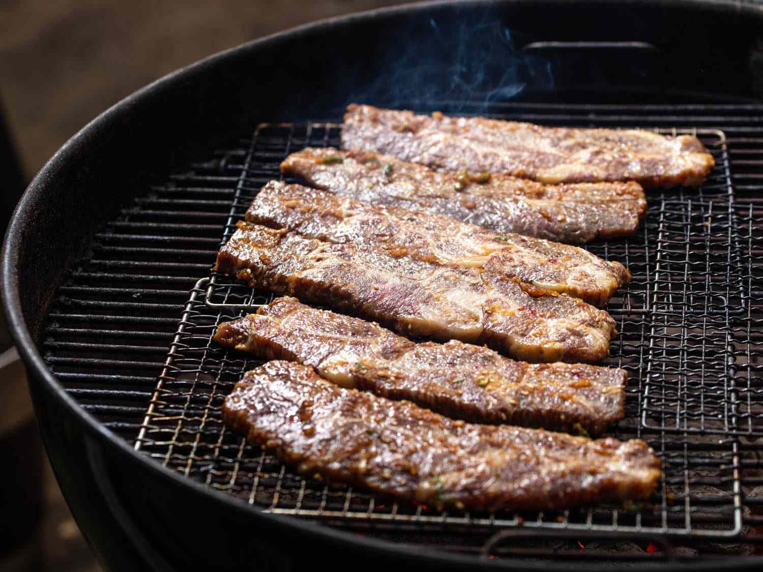 Beef galbi cooking on wire mesh racks set on a charcoal kettle grill.