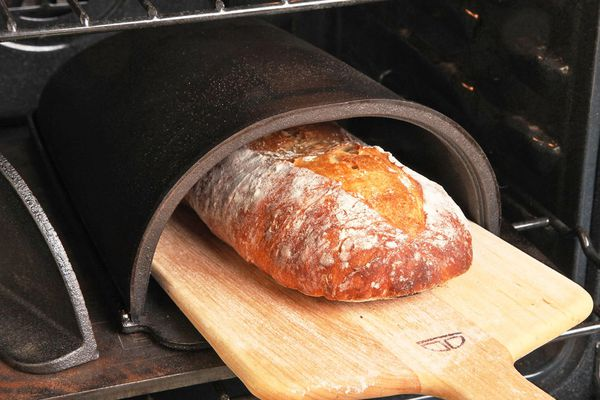 Removing a loaf of bread from a Forneau bread oven with a wood peel.