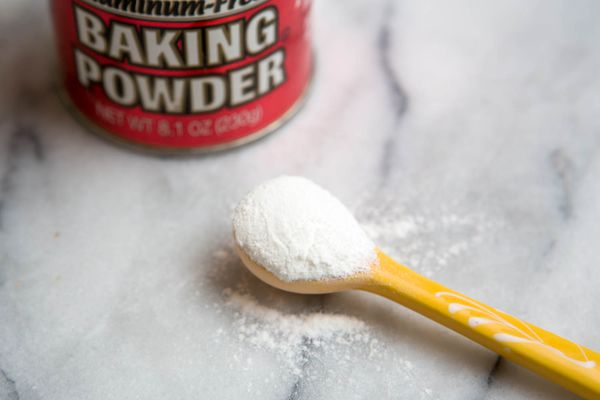 A container of baking powder next to a spoon full of baking powder.
