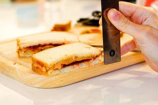 Measuring the thickness of a cut peanut butter and jelly sandwich on a wood cutting board.