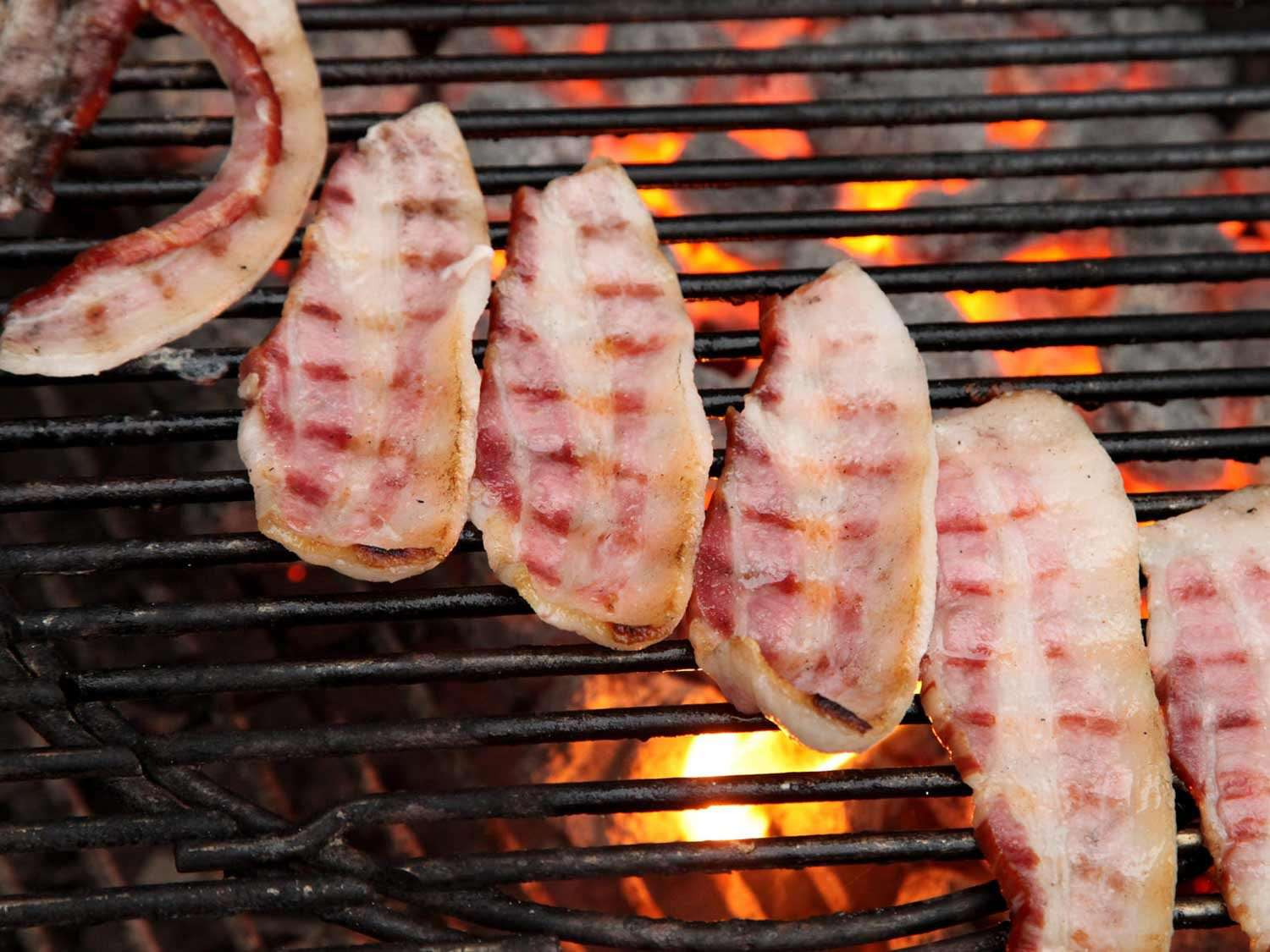 bacon on a charcoal grill over bright embers