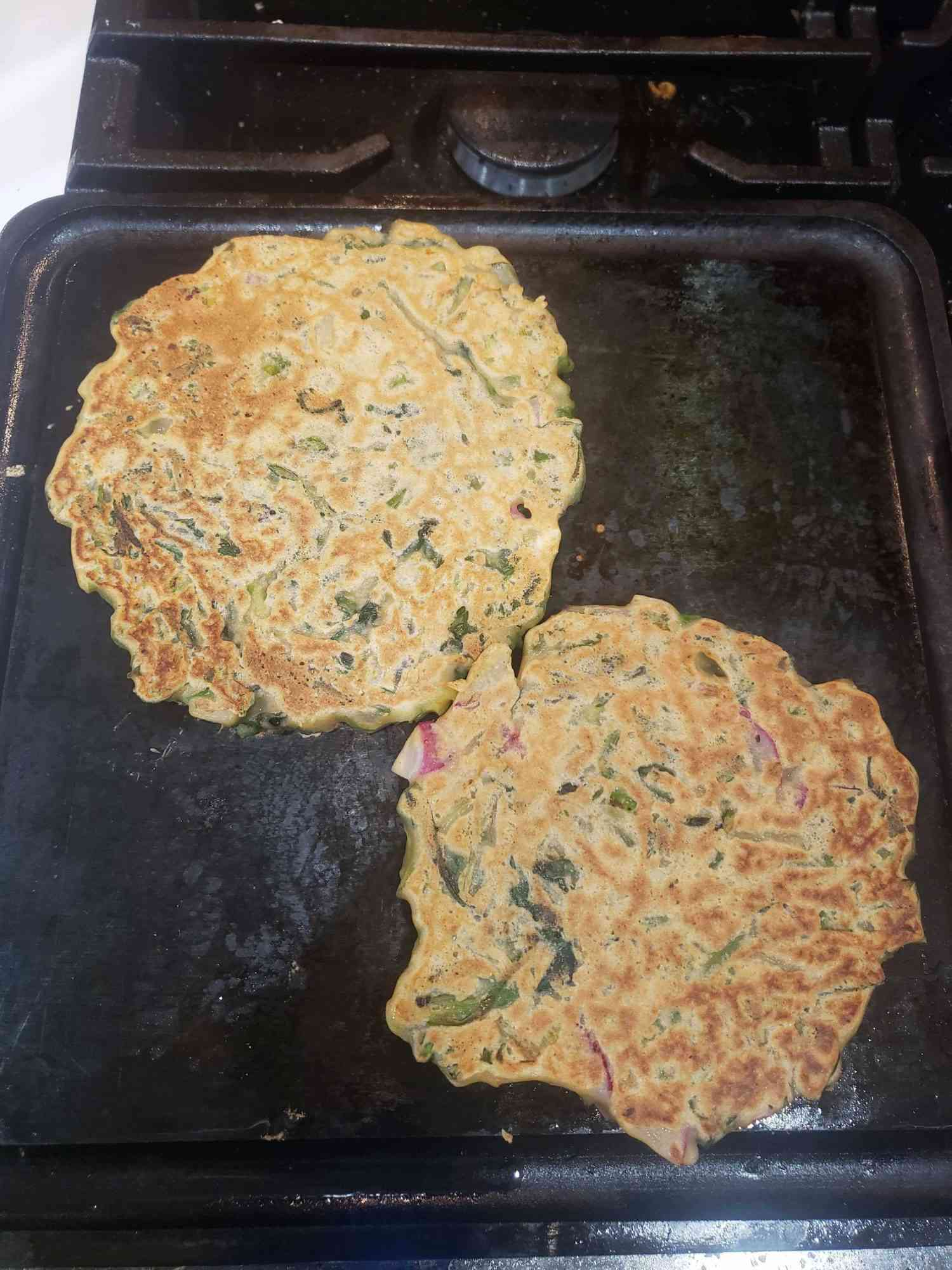 two savory pancakes cooking on a griddle