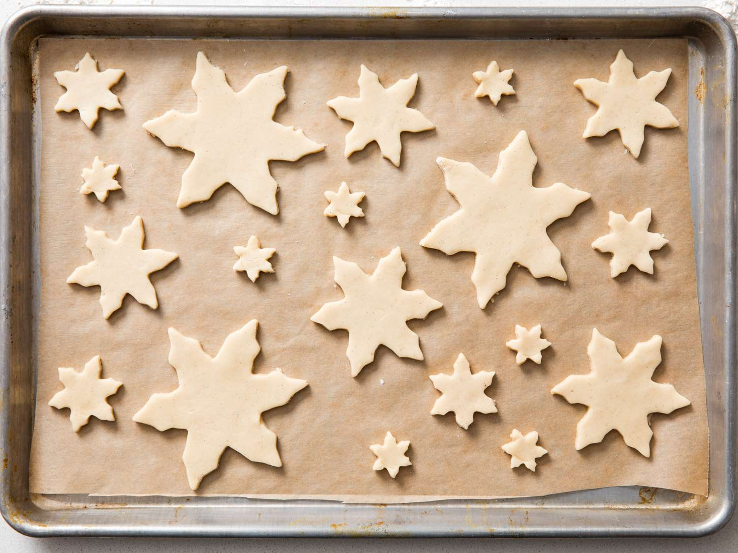 Sugar cookies on a piece of parchment in a baking sheet