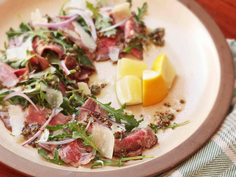 Half-eaten steak carpaccio salad (thinly sliced seared steak, arugula, shaved Parmesan, and vinaigrette) on a plate with lemon wedges