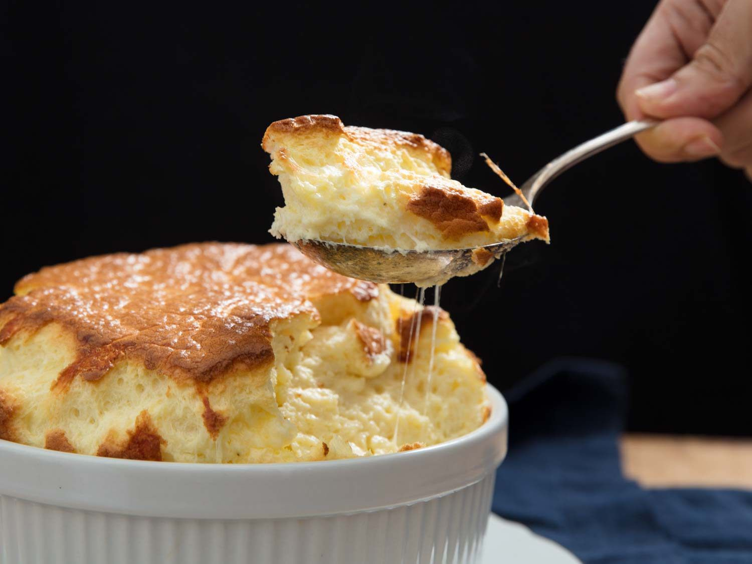 a spoonful of cheese soufflé with the large soufflé in the background