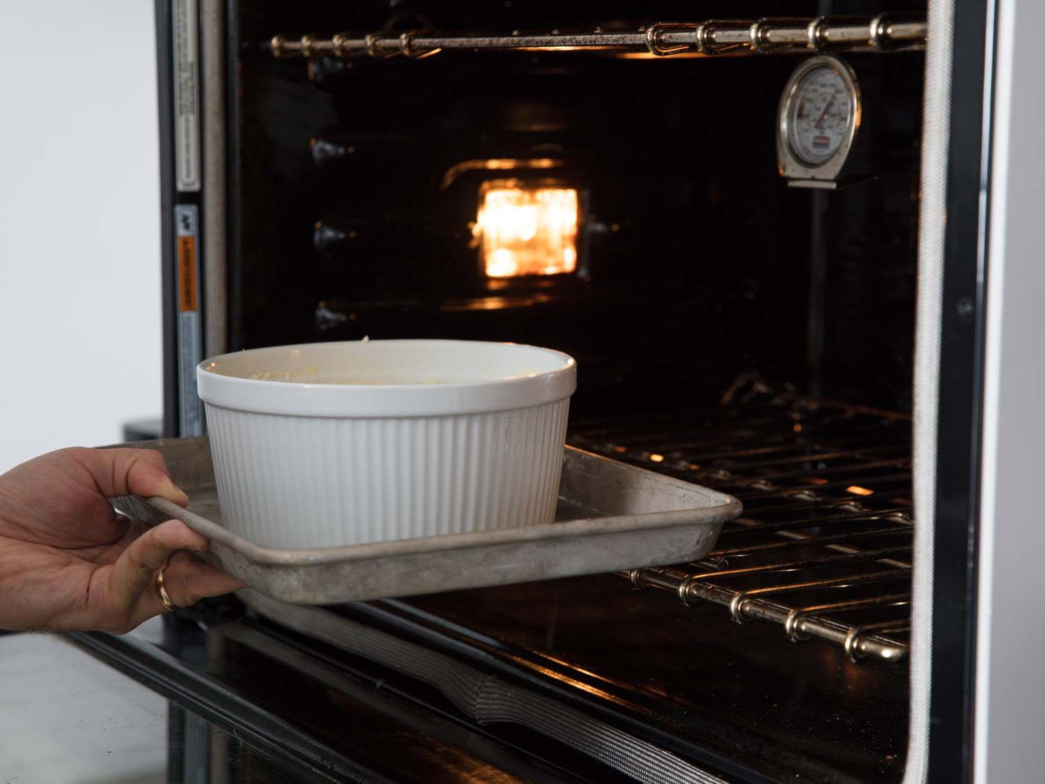 putting the cheese soufflé in the oven.
