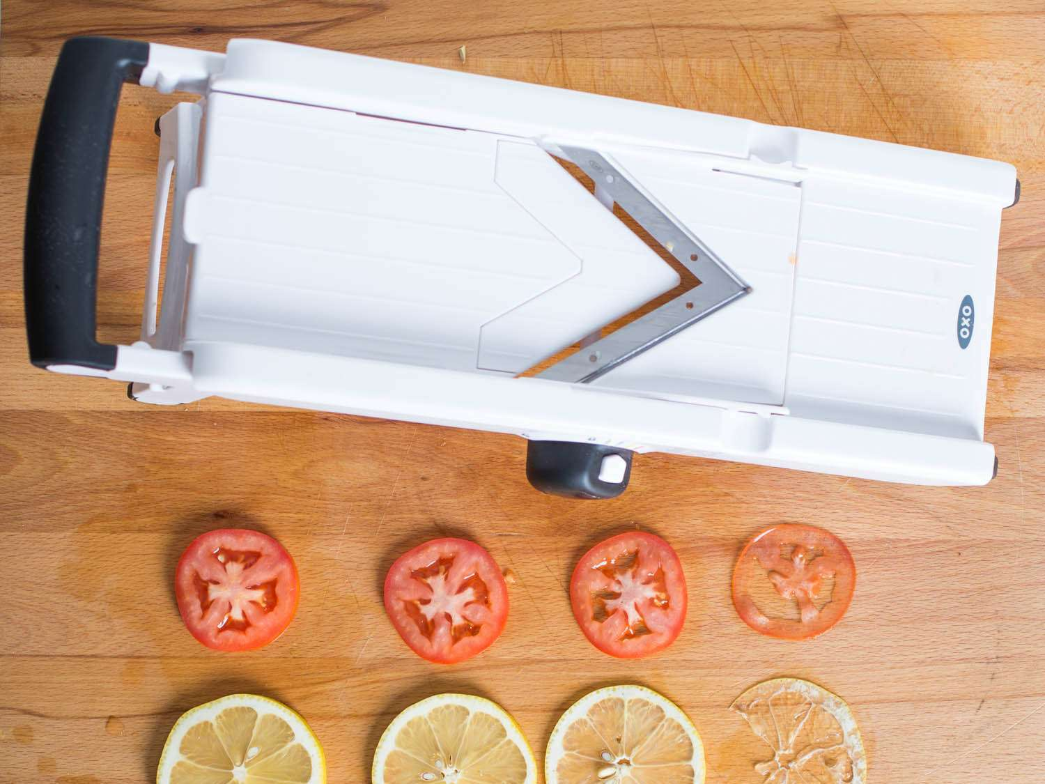 A mandoline v-slicer on a cutting board with sliced tomatoes and lemons.
