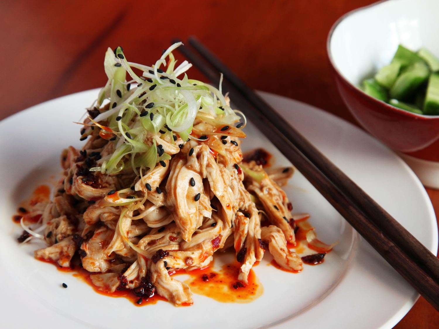 A plate of Sichuan shredded chicken salad topped with sliced scallions and black sesame seeds