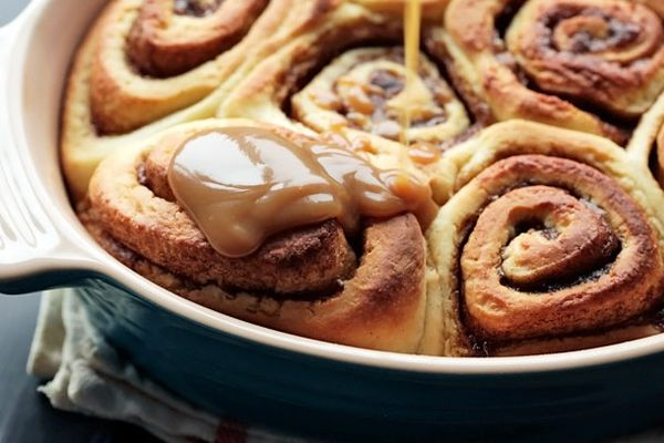 A ceramic baking dish with cinnamon sticky buns. Glaze is being drizzled over them.