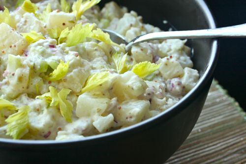 Bowl of Classic Potato Salad with a mayonnaise dressing, garnished with celery leaves