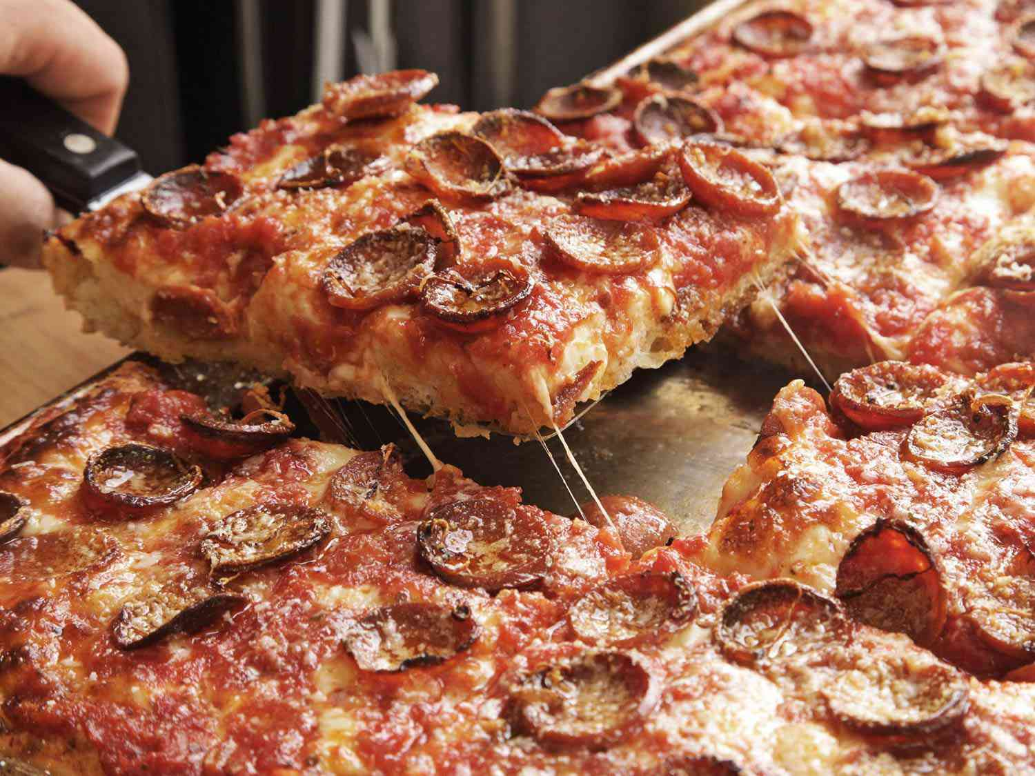 Removing a slice of pepperoni-topped Sicilian-style pizza from a sheet pan.
