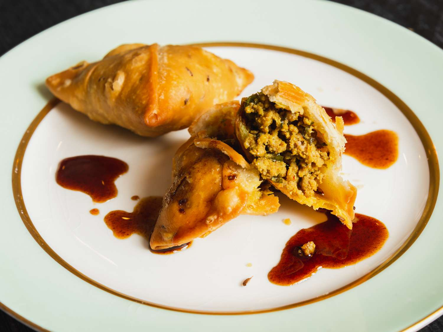 Two kheema samosas on a plate, one broken open to show its interior