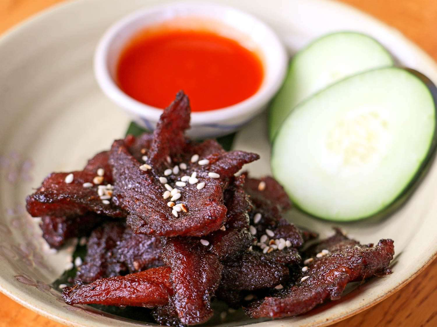 A stoneware plate of dark-red sun-dried pork (muu haeng) next to sliced cucumber and a small bowl of dipping sauce