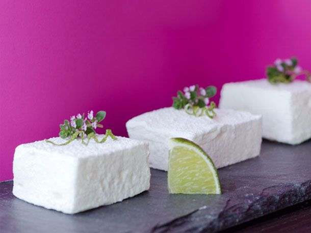 Pisco sour marshmallows on a piece of slate with a wedge of lime