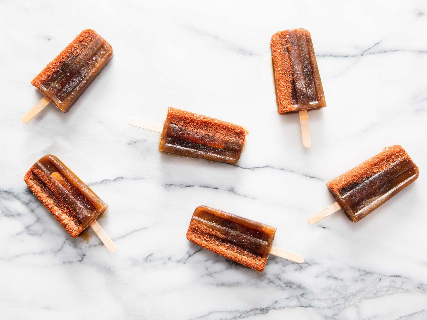 Several tamarind and palm sugar popsicles arranged on a marble slab