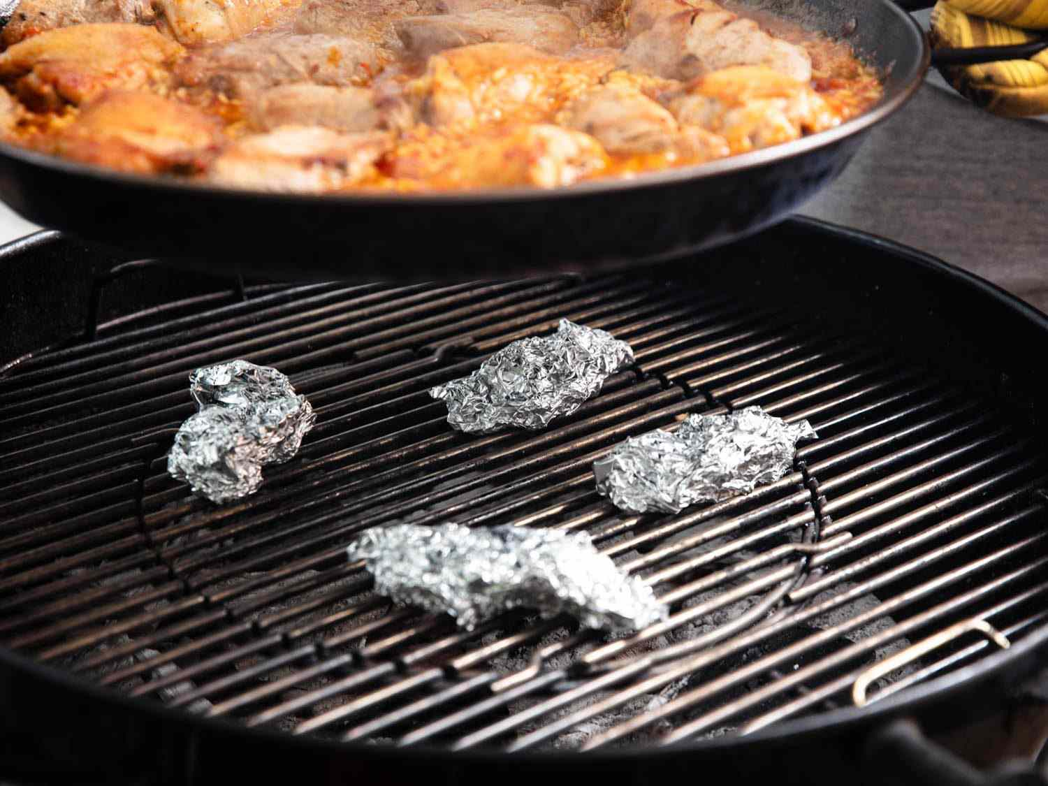 Pieces of aluminum foil can life the paella pan a little farther from the heat when necessary.