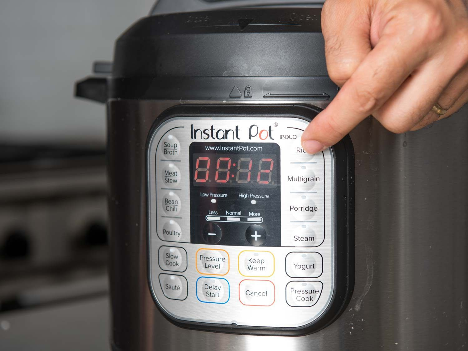 Person selecting rice function on Instant Pot multi-cooker