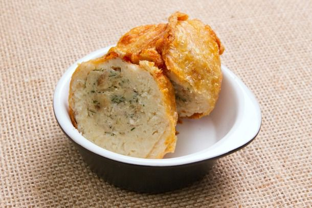 A small bowl holding two crispy deep-fried stuffed matzo ball halves, with the filling visible