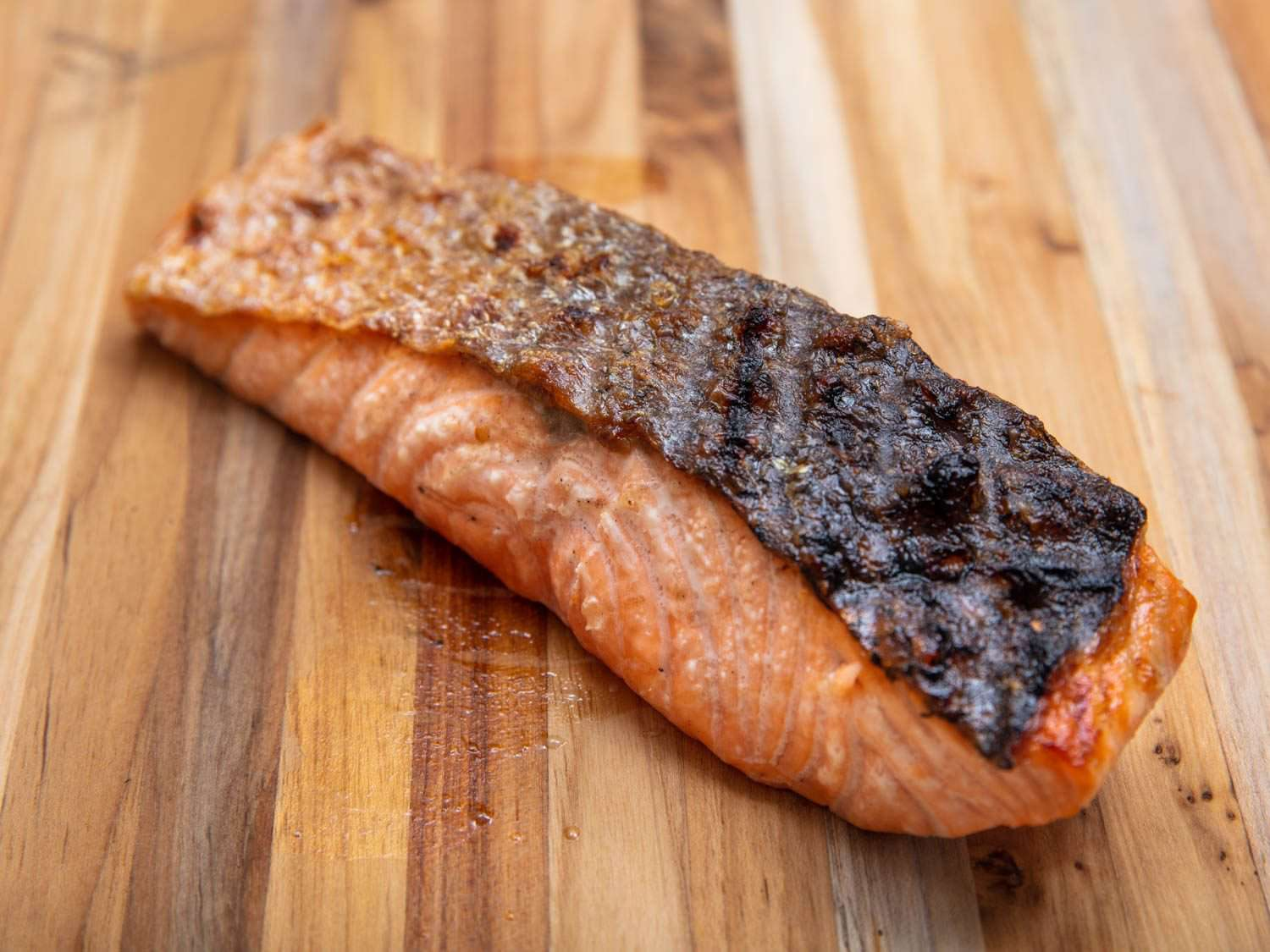 A finished grilled salmon filet on a cutting board, with the skin side up, showing the skin nicely browned and crispy and the fish cooked through