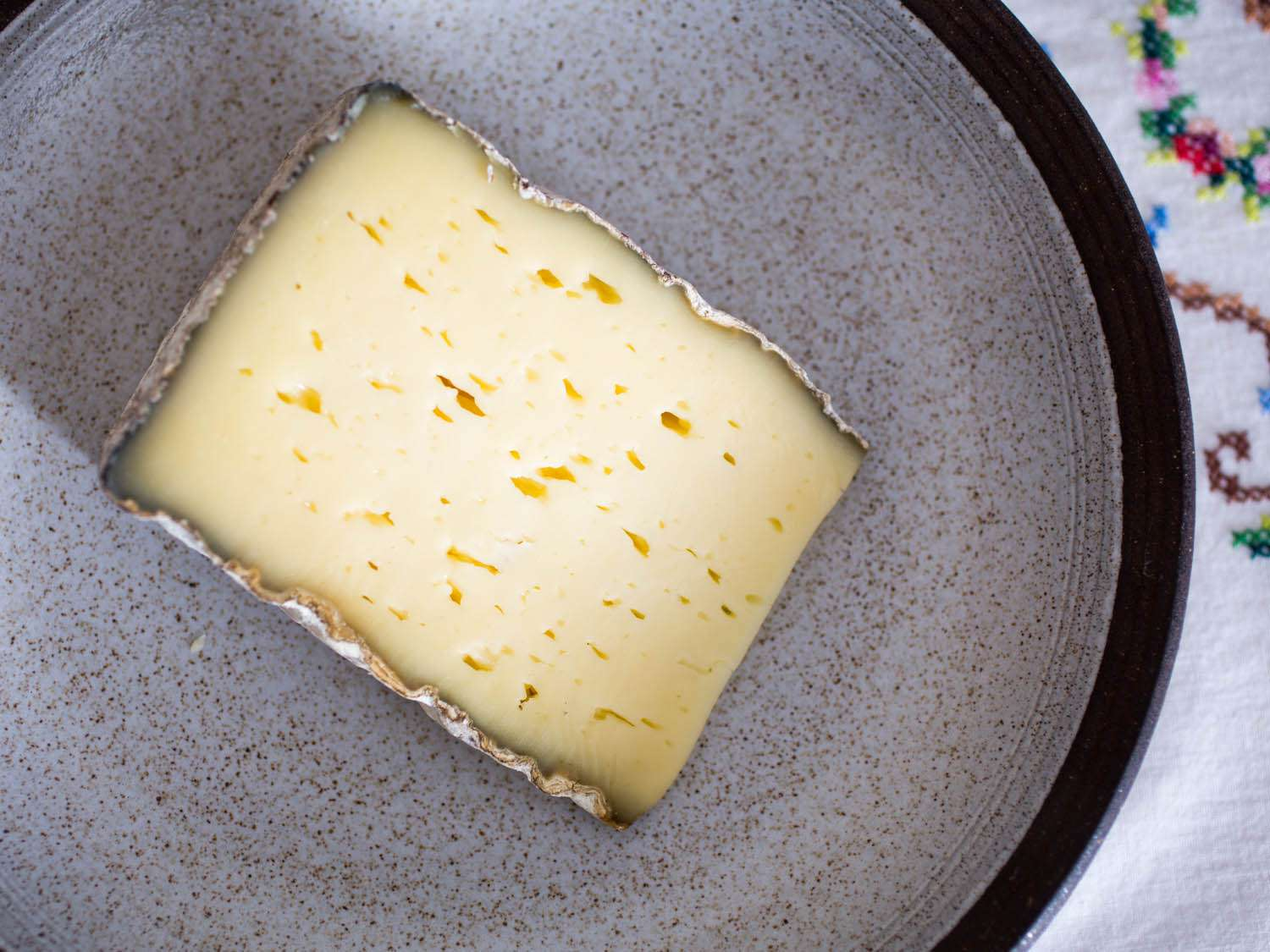 A wedge of Weinkase Lagrein cheese on a speckled gray plate.