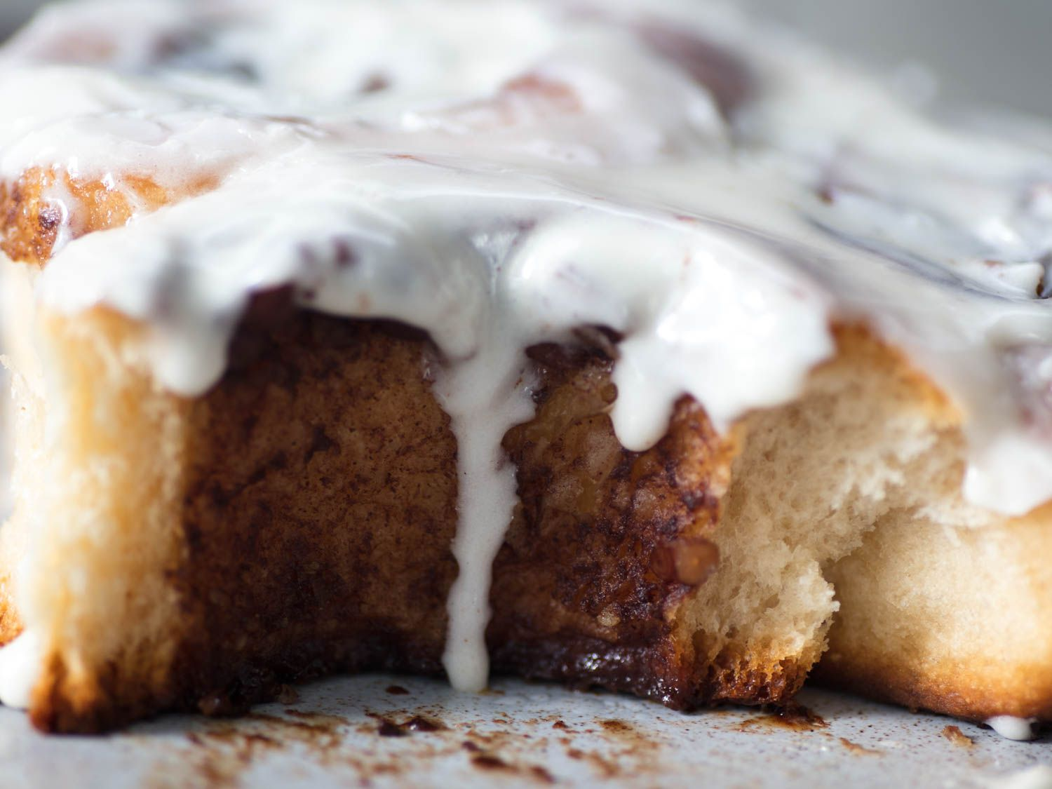Close-up photograph of a cinnamon roll with cream cheese icing dripping down.