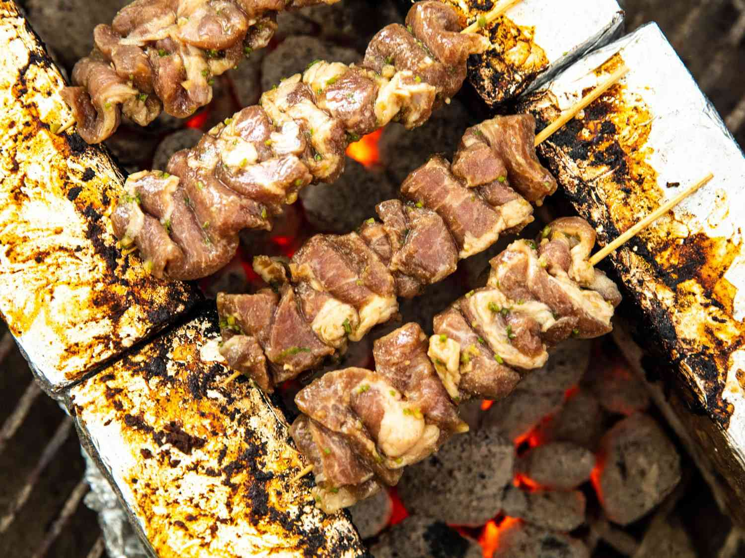 Four partially cooked pork Thai skewers on a brick stand over coals.
