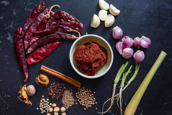 massaman curry paste with ingredients surrounding it