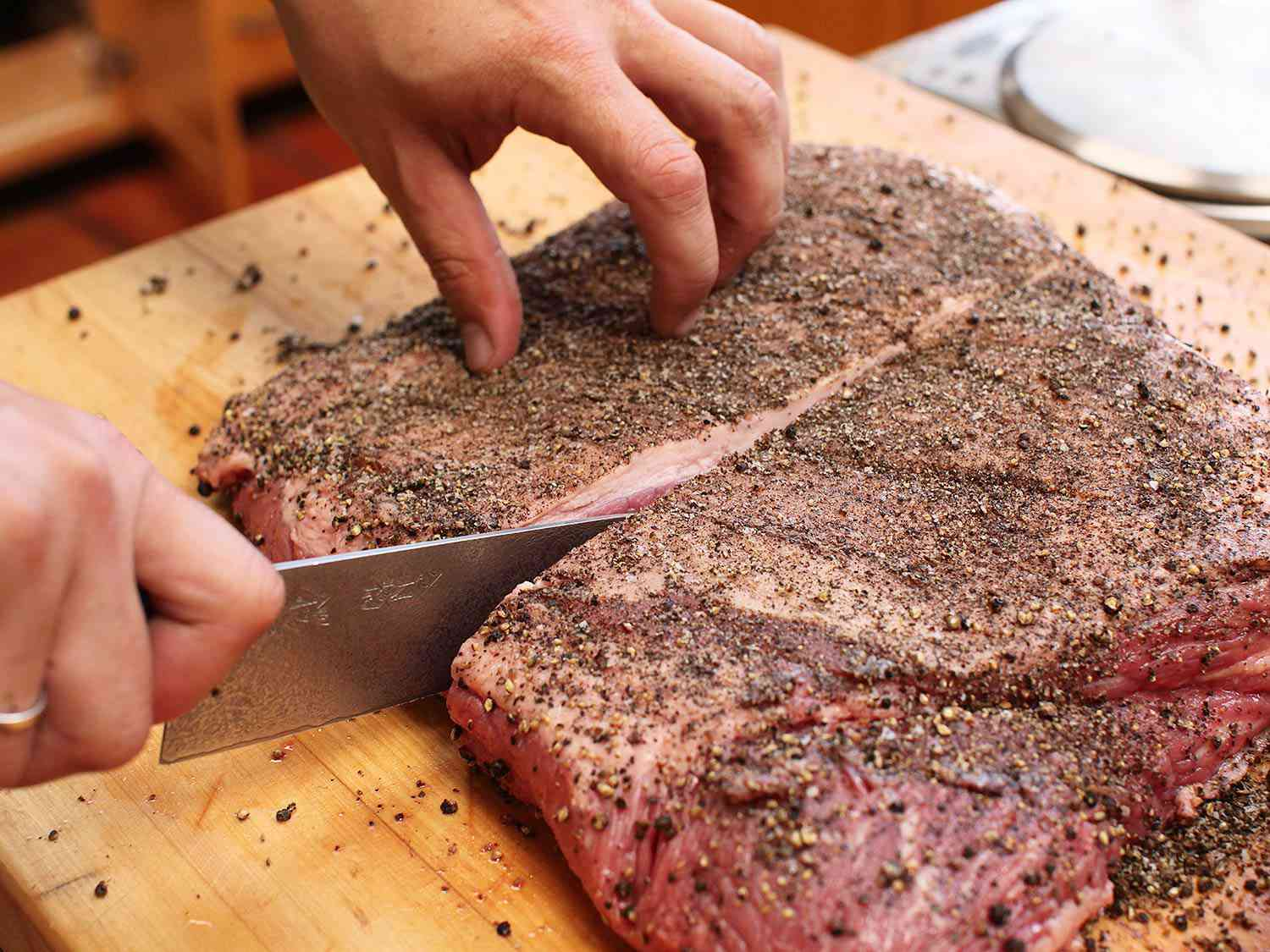 A knife slicing into a peppercorn-crusted brisket to cut it in half