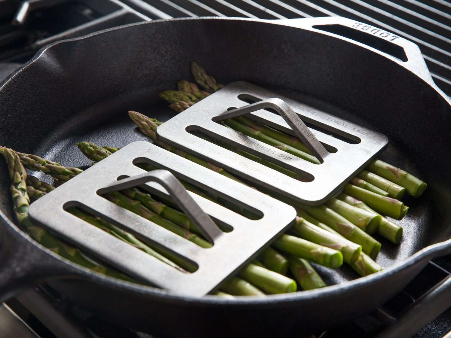 Maximizing contact between asparagus spears and a cast iron skillet with Chef's Press weights.
