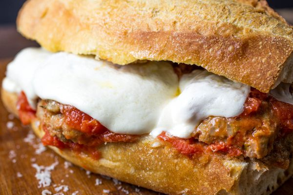An Italian American meatball sandwich with melted mozzarella cheese and tomato sauce.