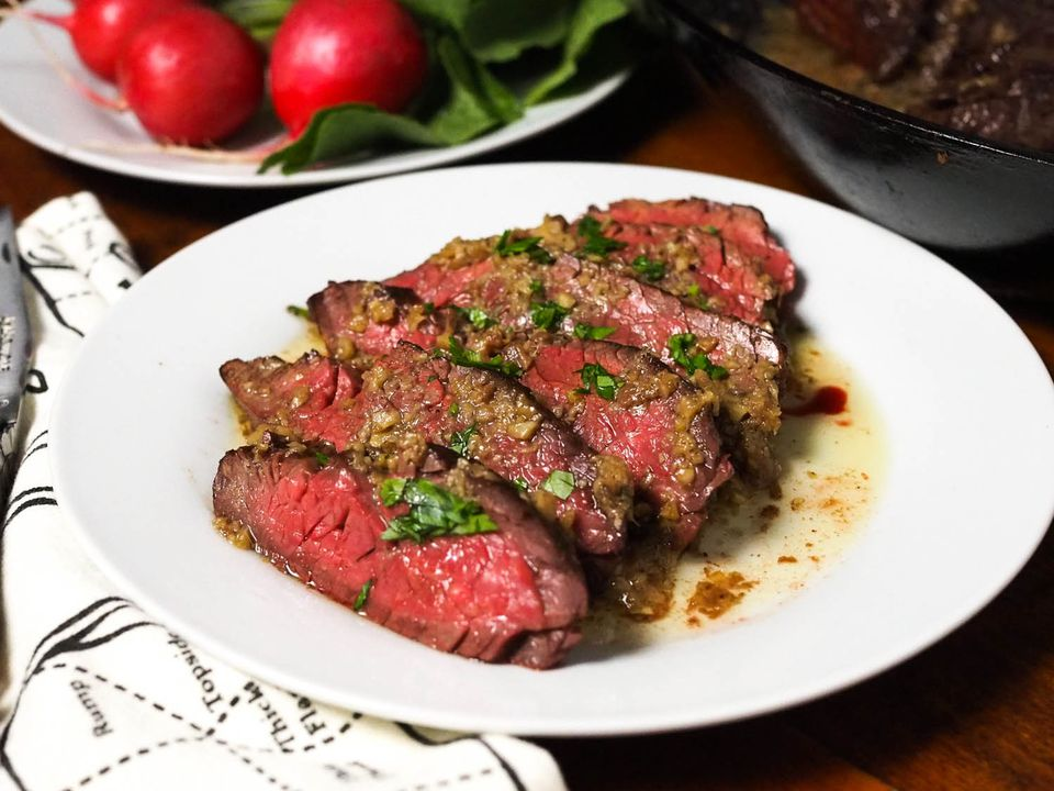 Rare, sliced steak with bagna cauda on a white plate.