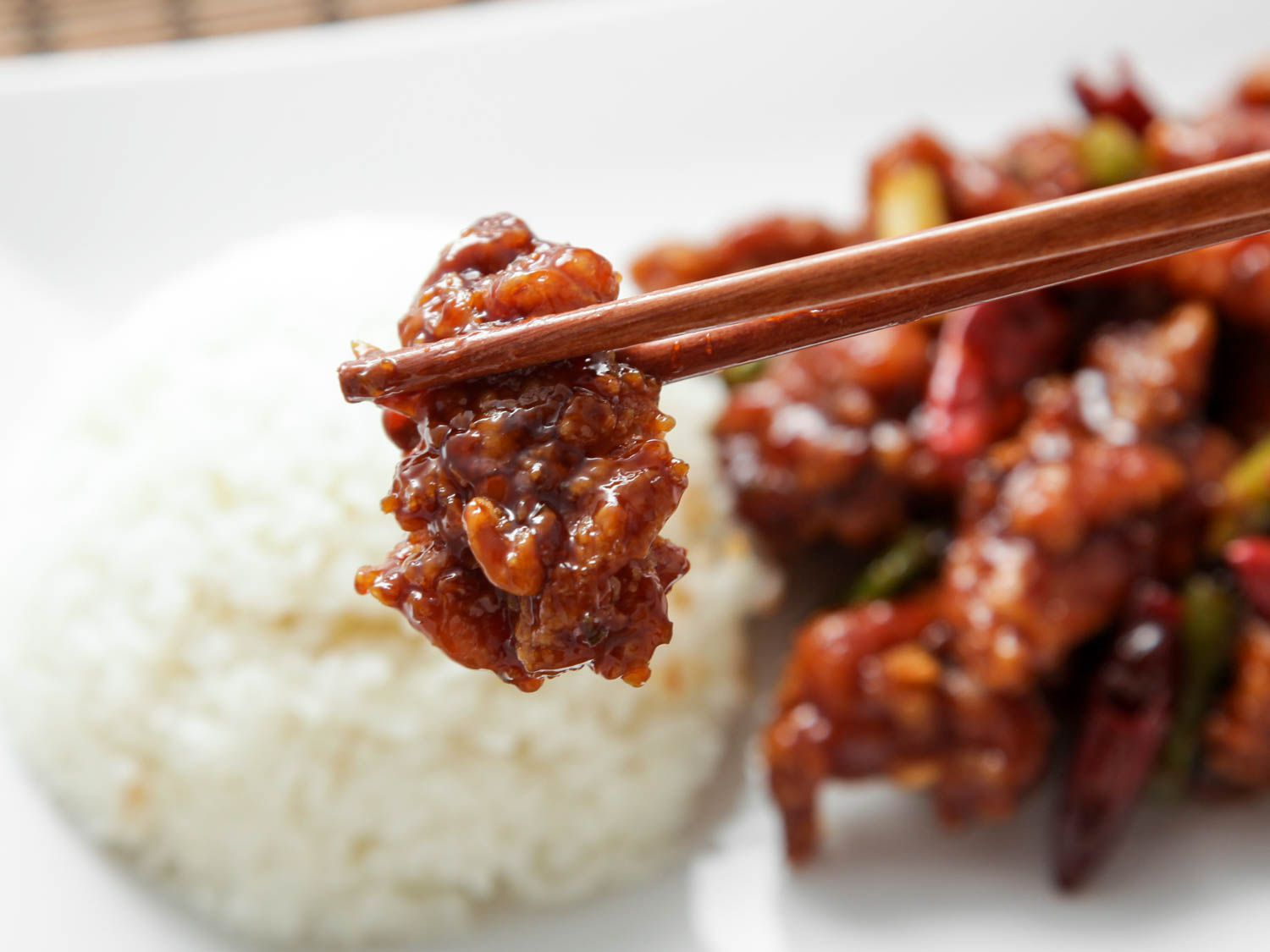Using chopsticks to hold a piece of General Tso's chicken over a bed of rice, with more chicken in the background.