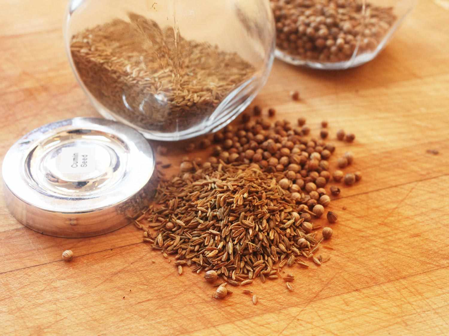Whole cumin and coriander seeds on a wooden cutting board with their jars in the background.