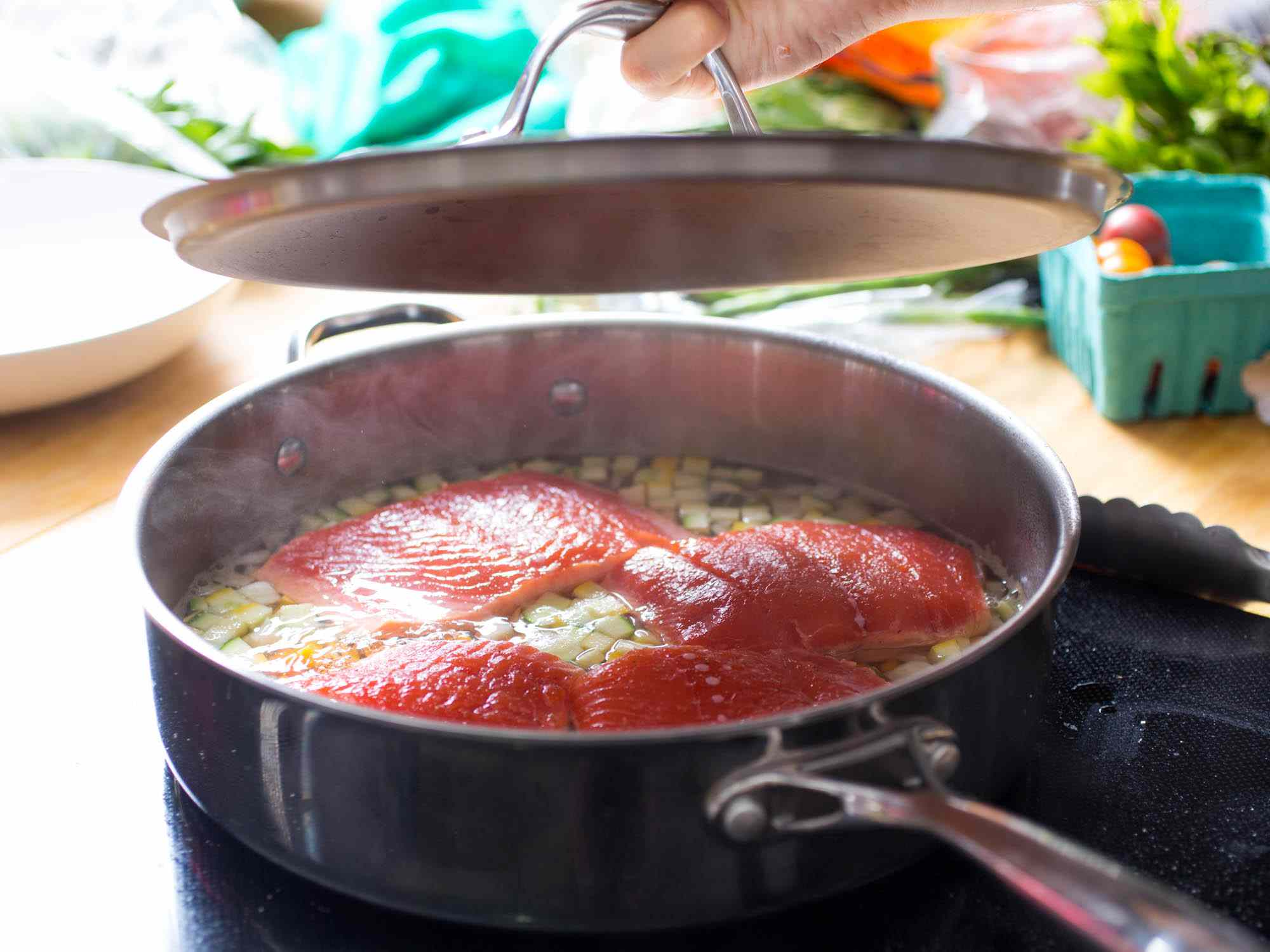 Four salmon fillets in a deep-sided skillet being cooked a la nage.
