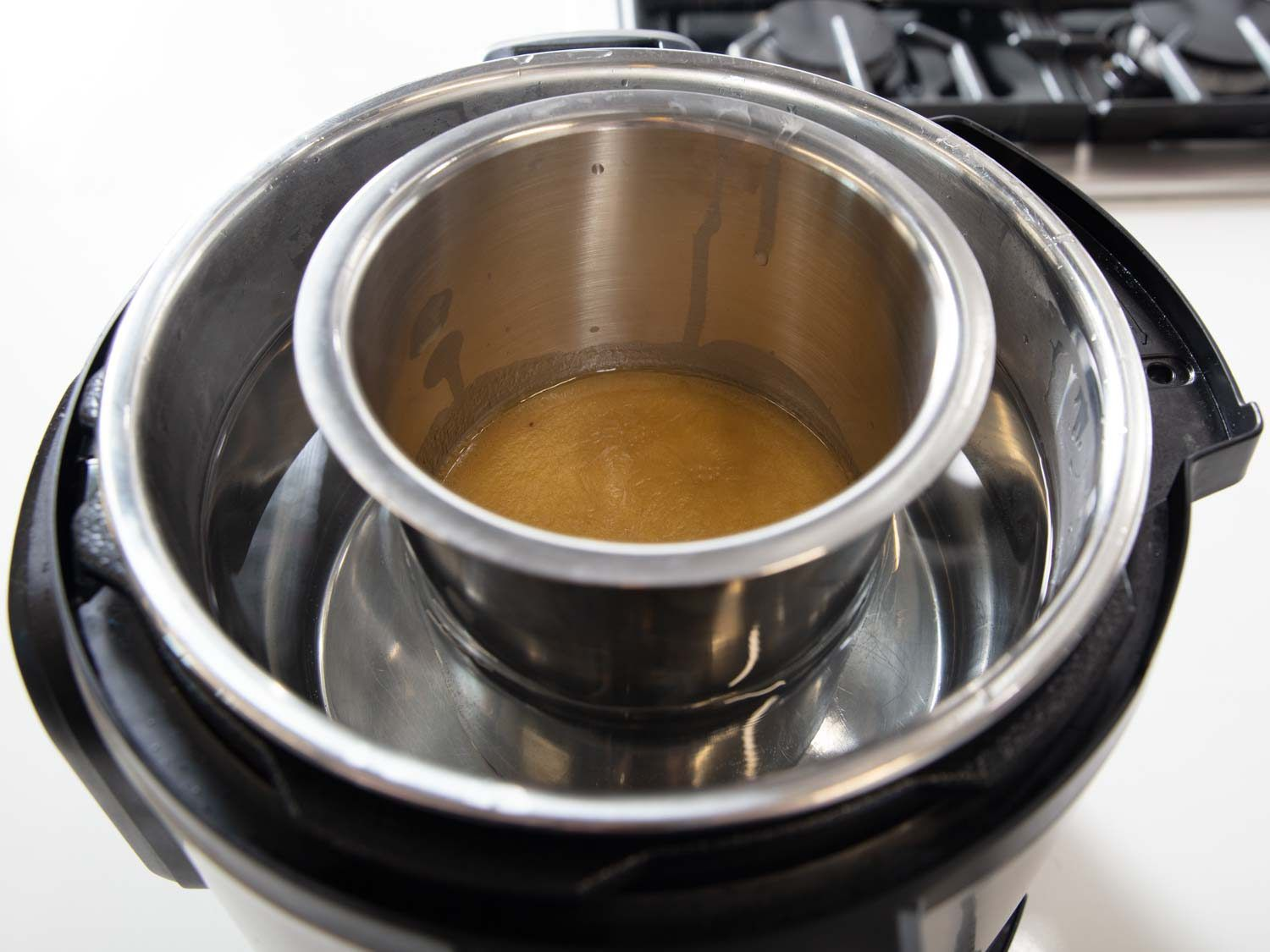 Here, a metal container holding gravy is sitting in a hot-water bath created using a multi-cooker set on its slow-cooker setting