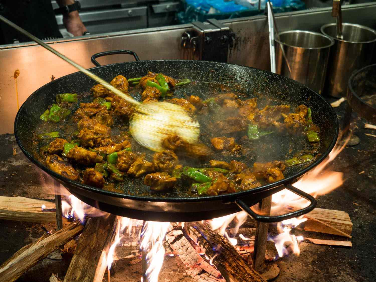 A traditional Valencian Paella being cooking at Mercado Little Spain: Pieces of rabbit and chicken, along with romano beans, are all cooked hard until deeply browned with tomato, before the stock and rice are added.