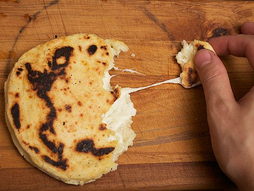 Tearing away a piece of a cheese filled arepa, with the cheese stretching out.
